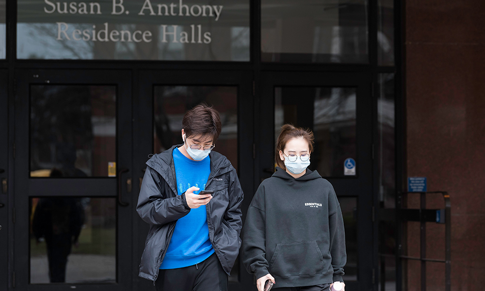 students in masks by residence hall