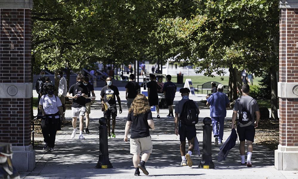 Masked students walk along campus path.