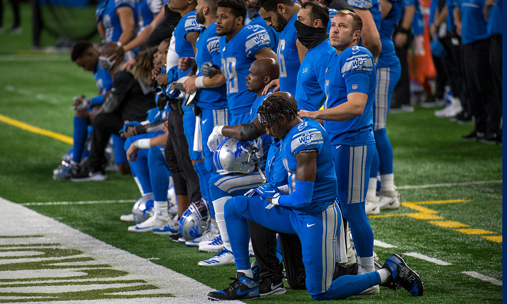 members of the Detroit Lions kneel before a game