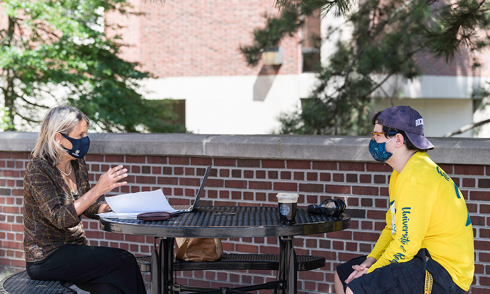 faculty member meeting outside with student