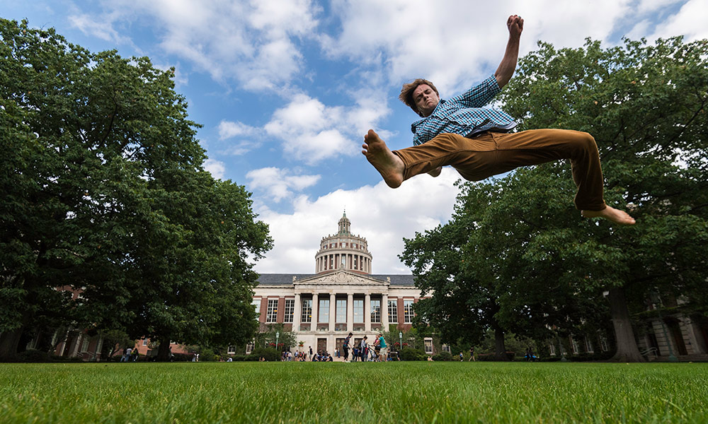 student does a leap on the quad that makes it look like he is jumping over Rush Rhees Library.