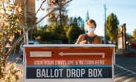 For election 2020, woman wearing mask deposits her vote at a drop box.