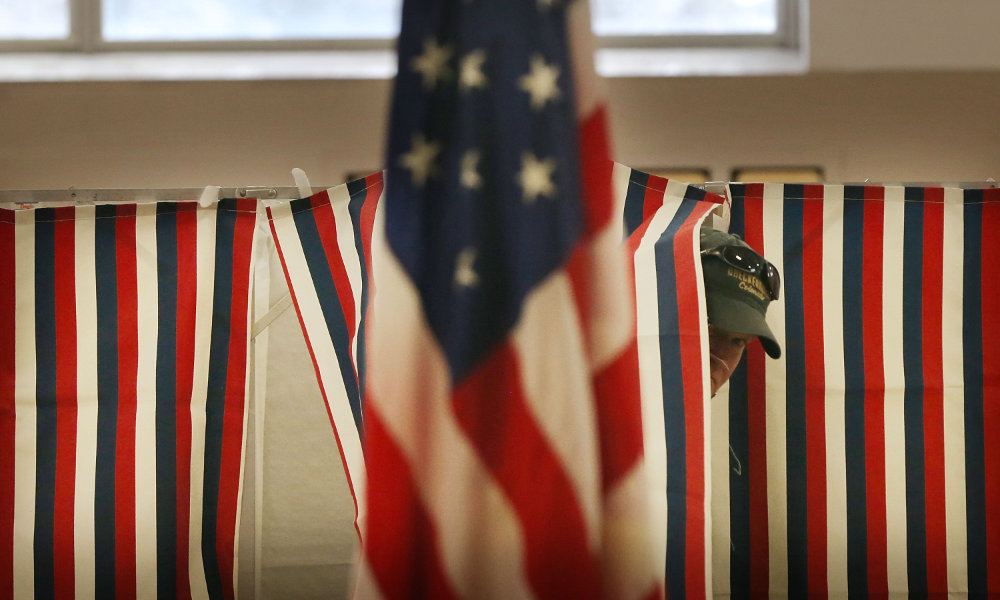 Voter peers from behind ballot curtain with an American flag in foreground.