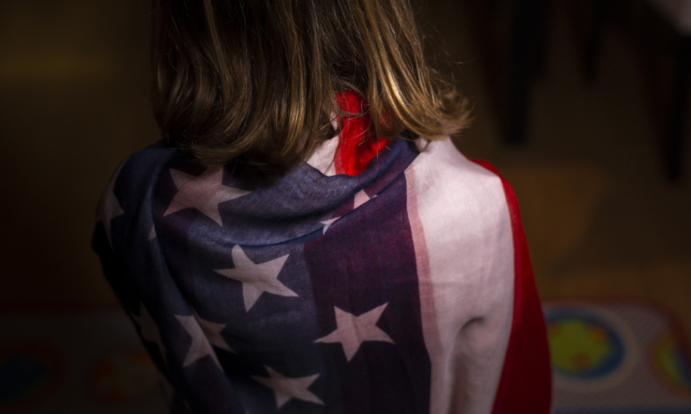 Anonymous young girl wrapped in the American flag.