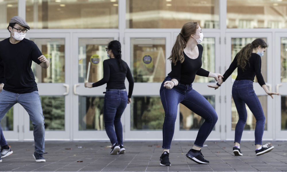 Students wear jeans and black tops while dancing on Wilson Commons porch.
