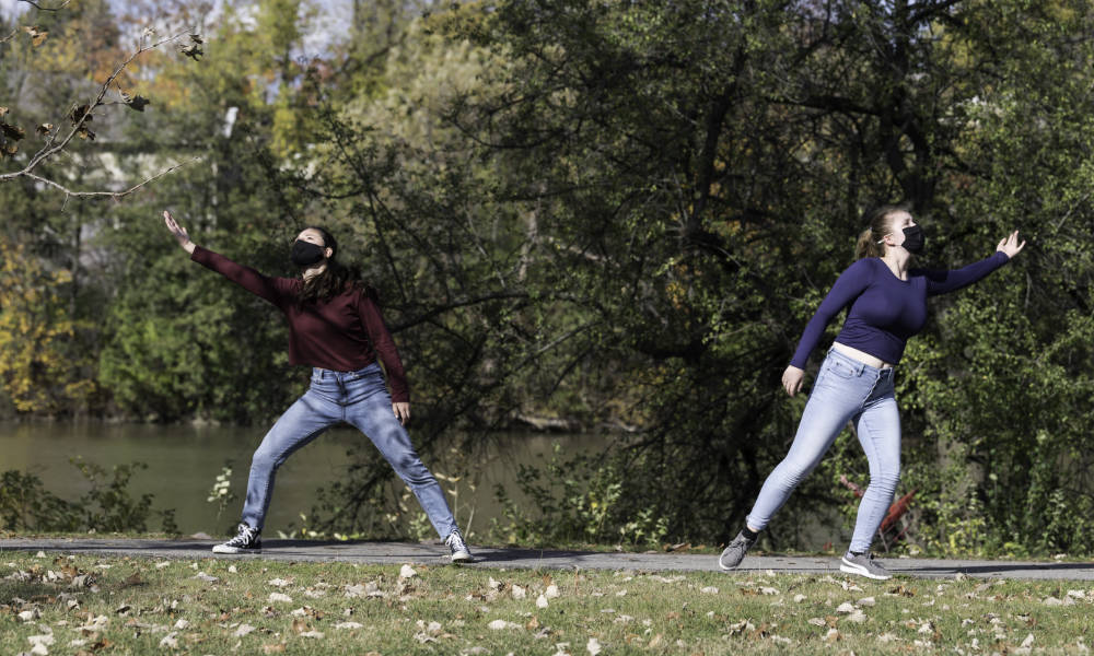 Two students dance on the sidewalk along the Genesee River.