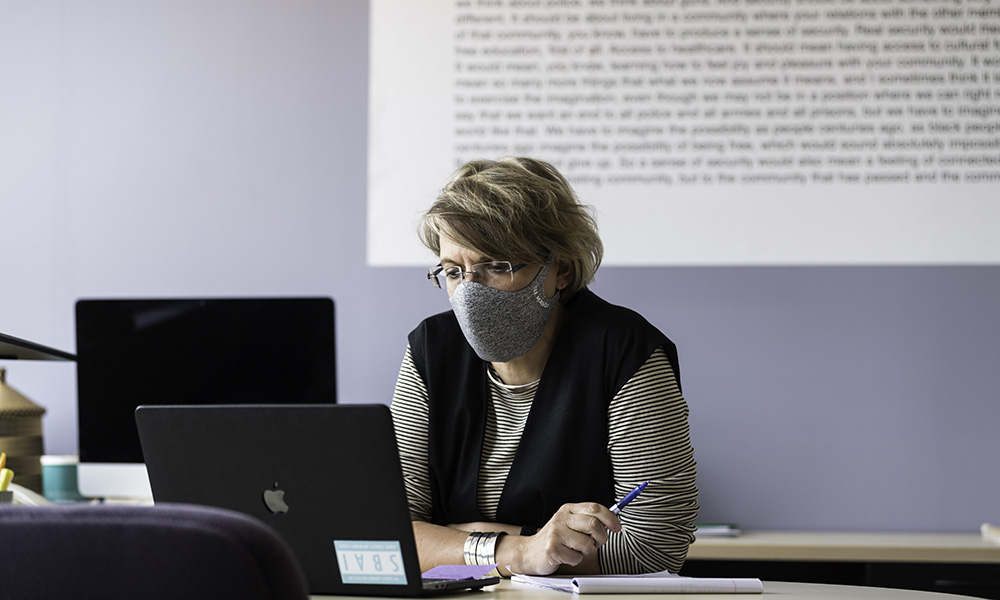 woman wearing mask looking at a computer