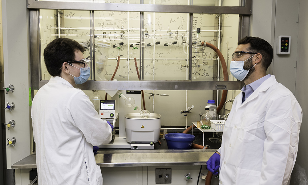 a professor and student talking to each other in a lab