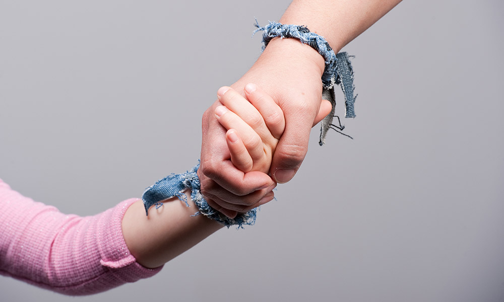 Hands of a child and a young adult clasped together.