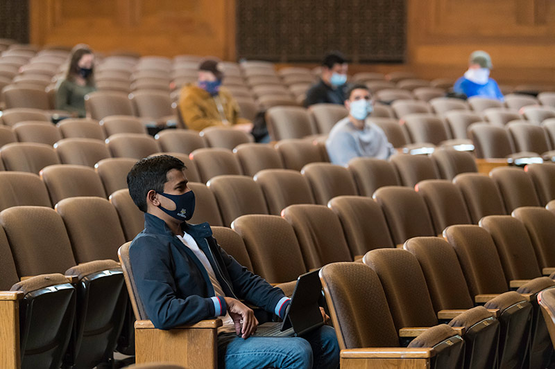 students sitting in large theater, socially distanced, wearing masks.