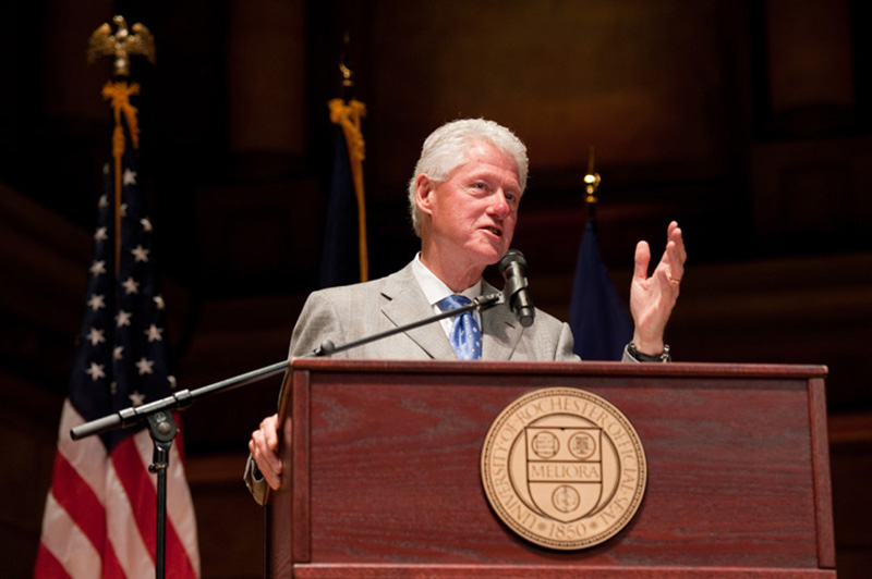archival photo of Bill Clinton speaking behind a podium with a University of Rochester seal.