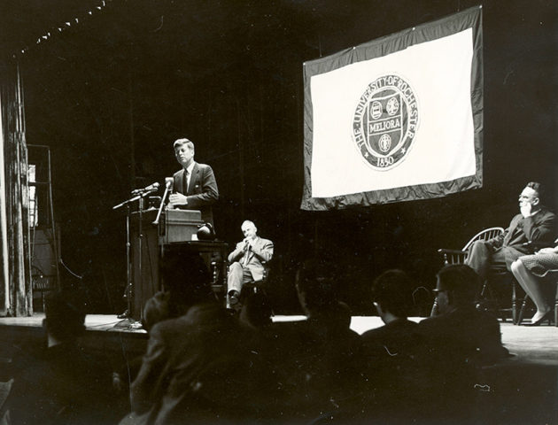 archival photo of JFK speaking at a podium in front of a University of Rochester flag.