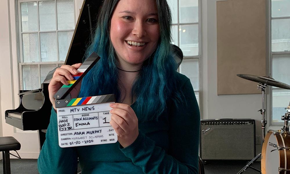 Emma Chang holding a film slate marker labeled MTV NEWS