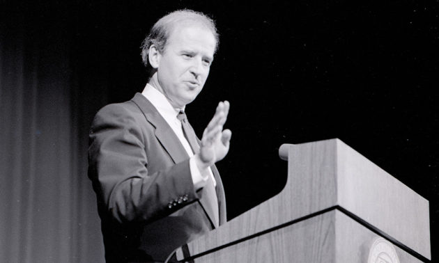 archival photo of Joe Biden speaking at a podium.