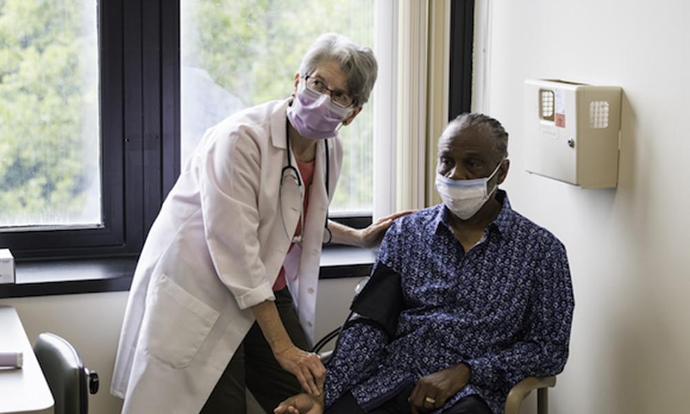 nurse takes patient's vital signs.