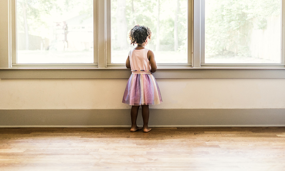 Black child in pink dress looks out a brightly lit window.