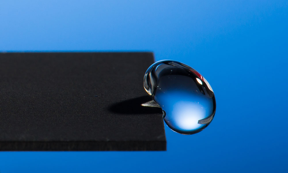 close-up of water droplet on edge of metal surface