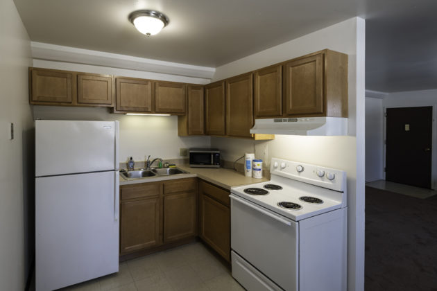Apartment kitchen with refrigerator, sink, stove, and cabinets.