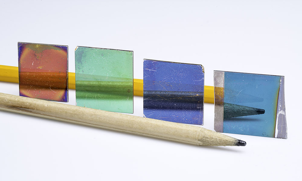 A pencil sits in front of four colored glass plates.