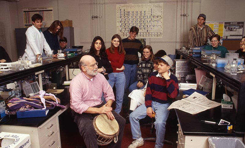archival photo of Professor Hattman in his lab, surrounded by a group of students, as he plays an African drum.