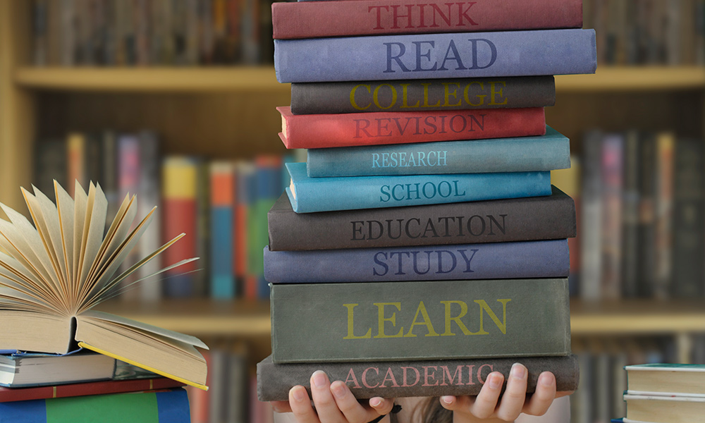 image of student holding stack of books
