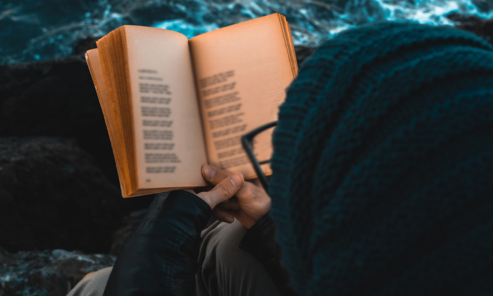 Person with glasses reads by the sea.