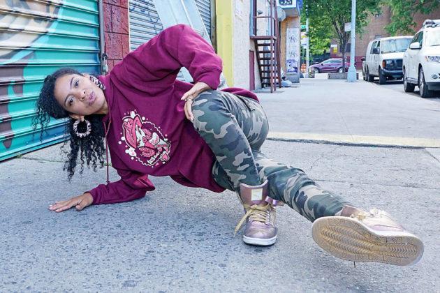 Ana Rockafella Garcia poses mid-dance on a city street.