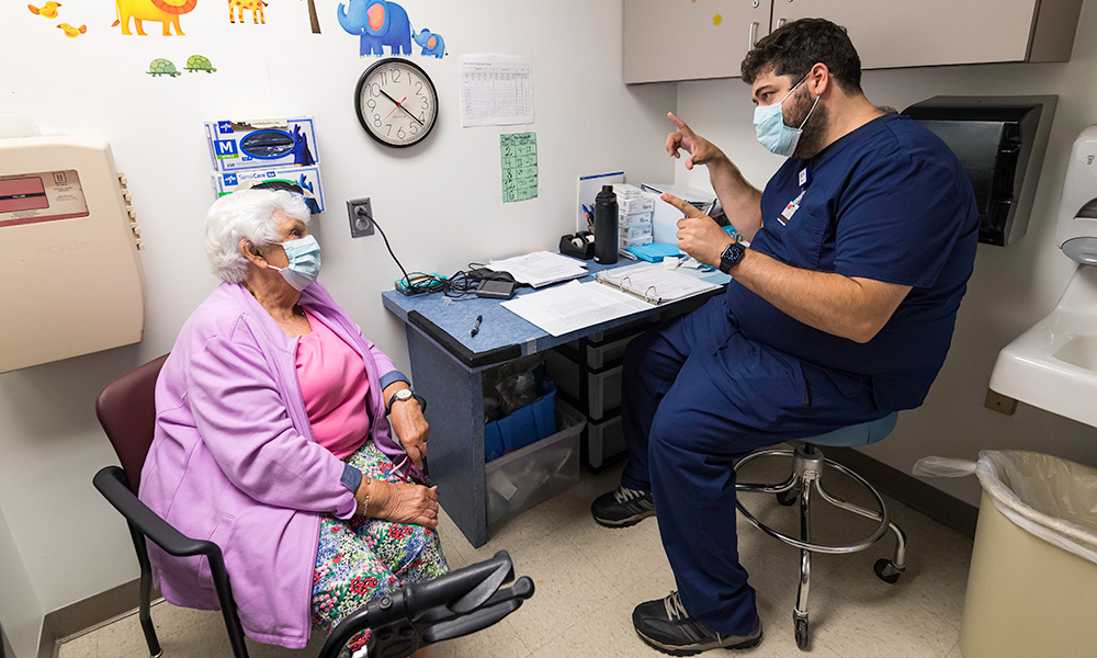 patient wearing a mask speaks to a nurse who is also wearing a mask and speaking to her about a vaccine trial
