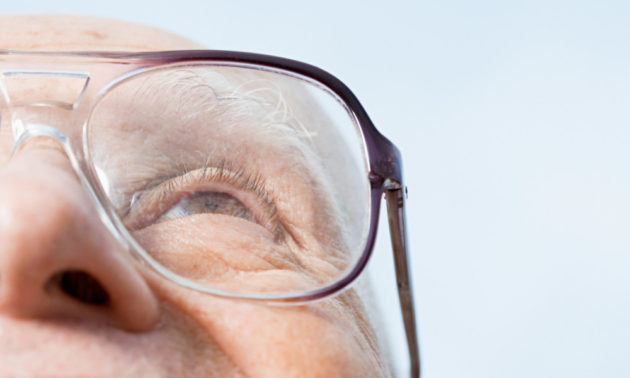 Senior man, half out of the frame, wears glasses and looks up with a light blue sky in background.