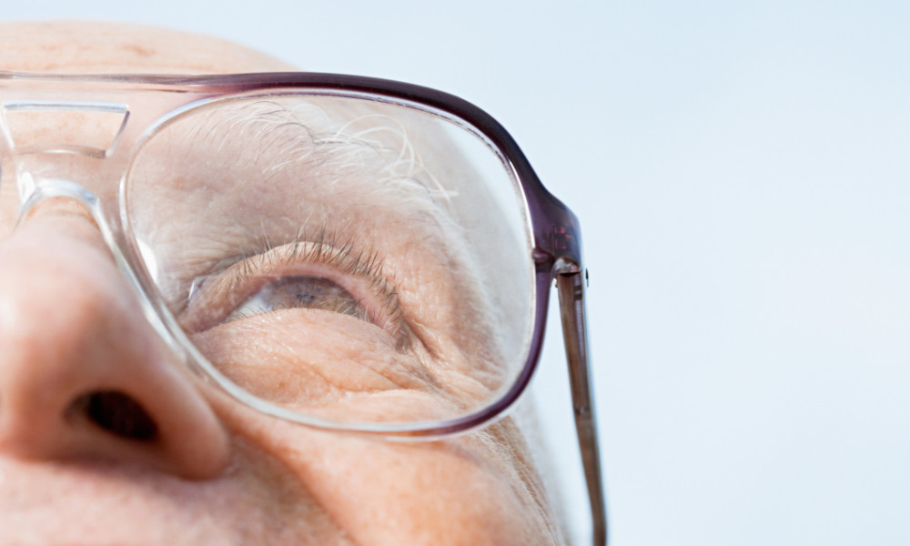 Senior man, wears glasses and looking up, suffering from macular degeneration