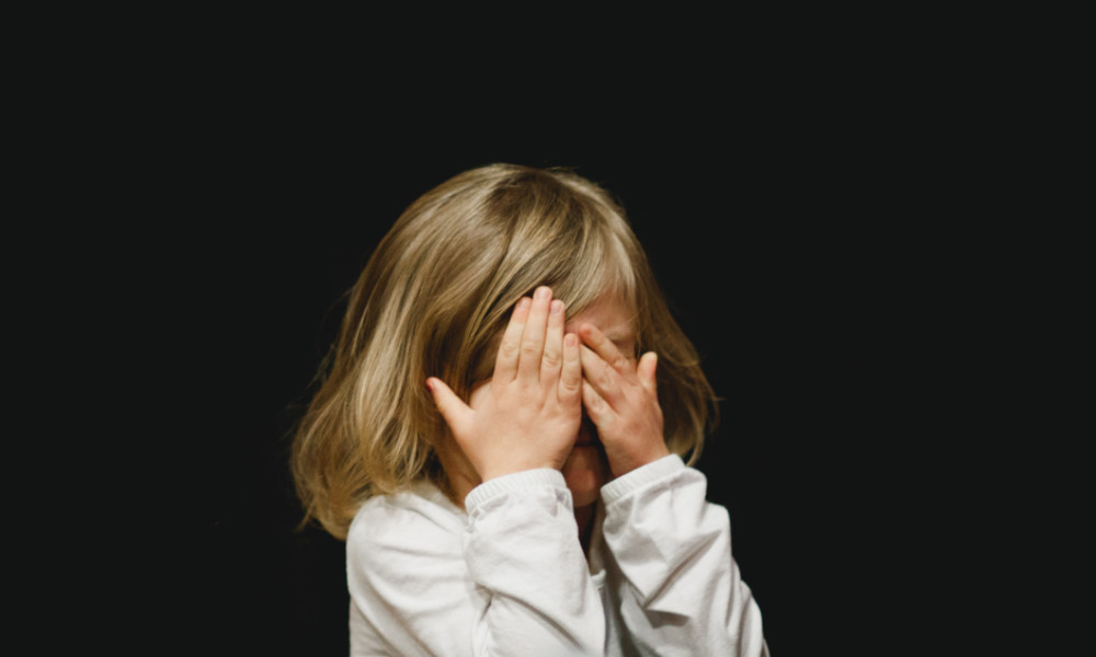 Young blonde girl against black background wears white long sleeve shirt and covers her eyes.