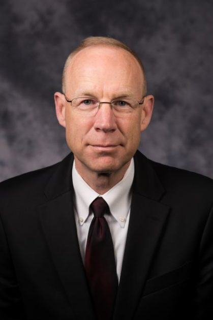 Mark Fischer in black suit and tie with white collared shirt.