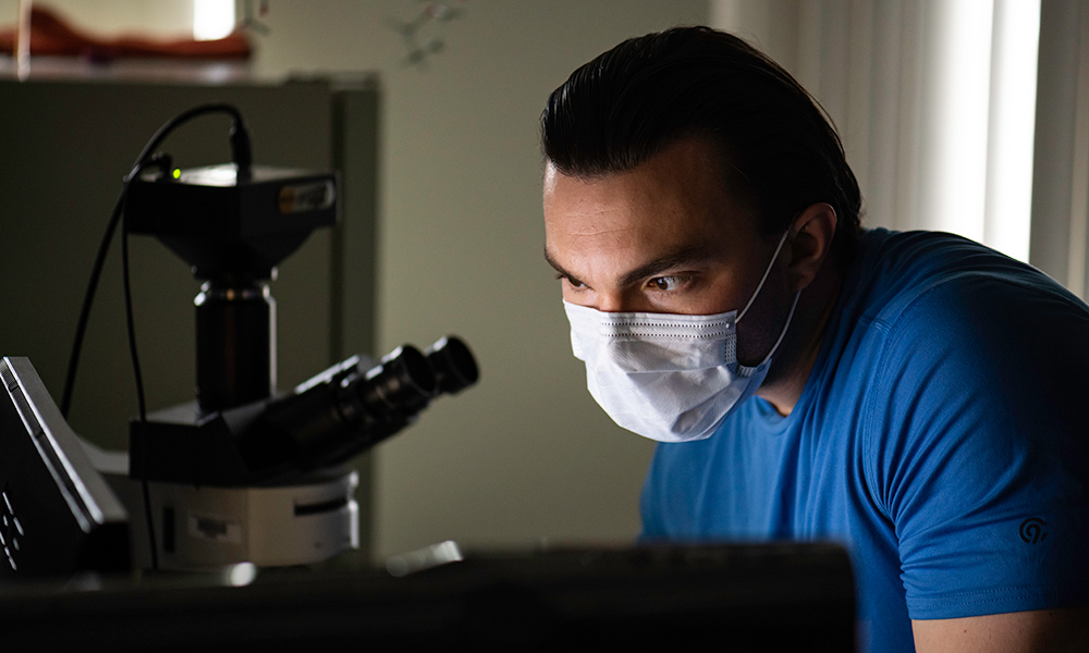 Jeffrey Beard wears a mask and blue shirt while leaning in near a microscope.