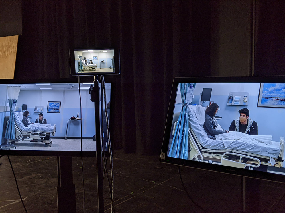 Three computer screens, two large and one small, showing the same hospital bed scene with two actors.