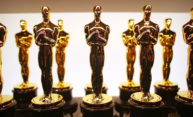 Two rows of Academy Award statuettes lined up backstage.