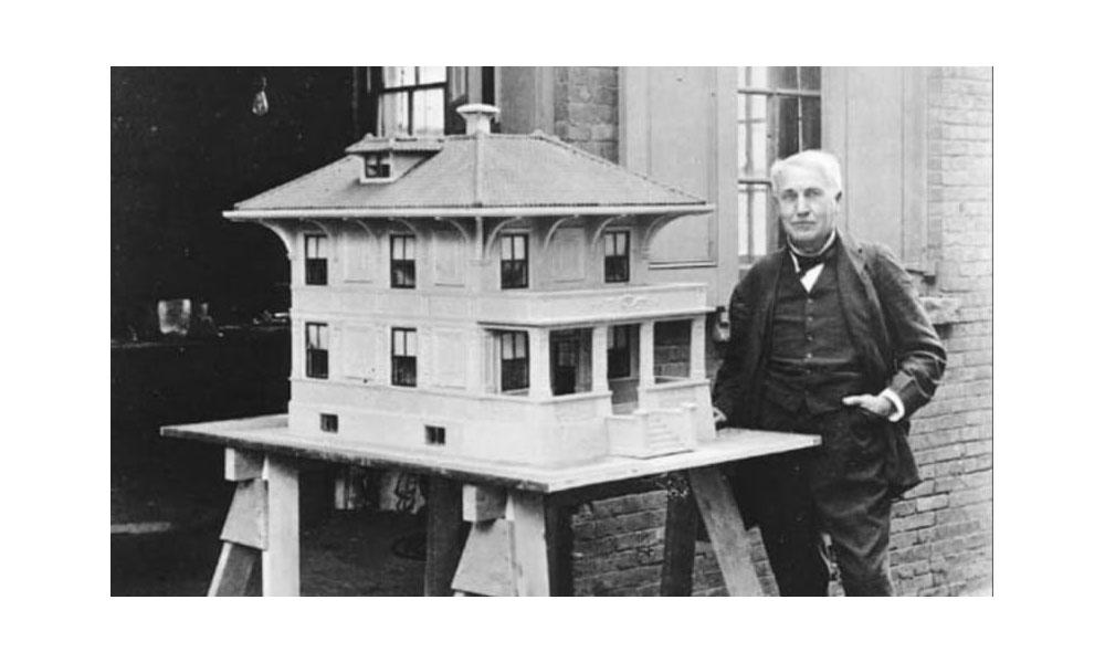 Thomas Edison standing next to model house.