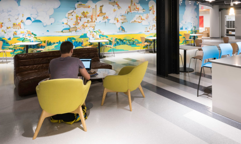 Seen from behind, a man sits in a yellow chair and looks at his laptop in the NextCorps business incubation space at Sibley Square, complete with colorful mural and modern shared workspaces.