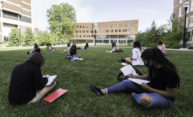 Ten masked and distanced students sit outside on the Hajim Quad lawn surrounded by red brick buildings and blue skies.
