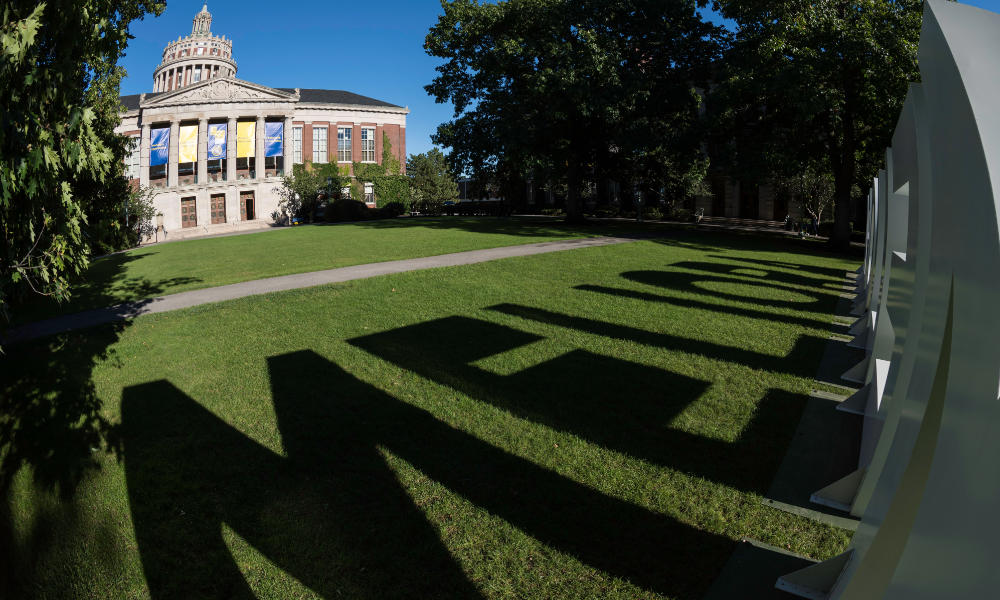 The Meliora letters cast a shadow on the Eastman Quadrangle lawn with Rush Rhees Library in the background.