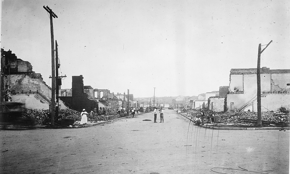 historical image looking down a street with burned out building lining both sides.