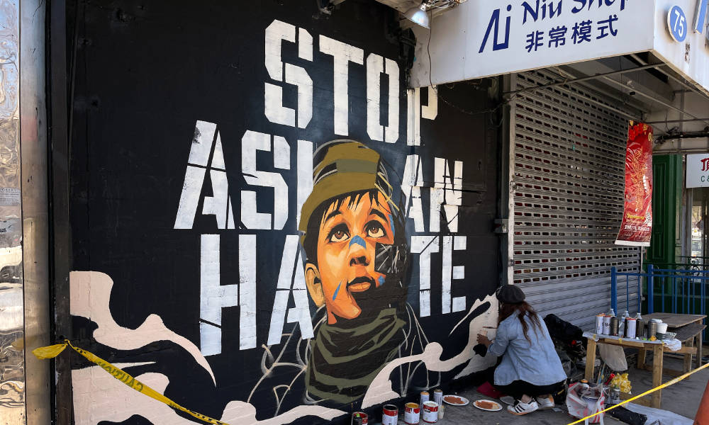 """An assistant paints part of a mural by artist Dragon76 that reads """"Stop Asian Hate"""" in Manhattan's Chinatown."""