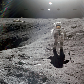 Astronaut collects lunar samples with a parked lunar roving vehicle in the background.