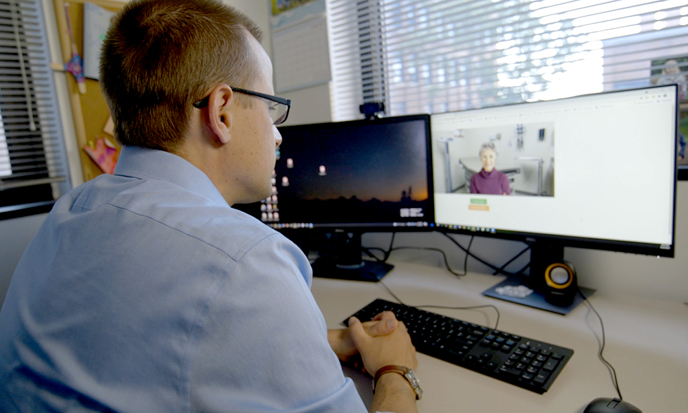 person sitting at a computer looking at a screen with an AI avatar that looks like another person, demostrating having an online conversation.