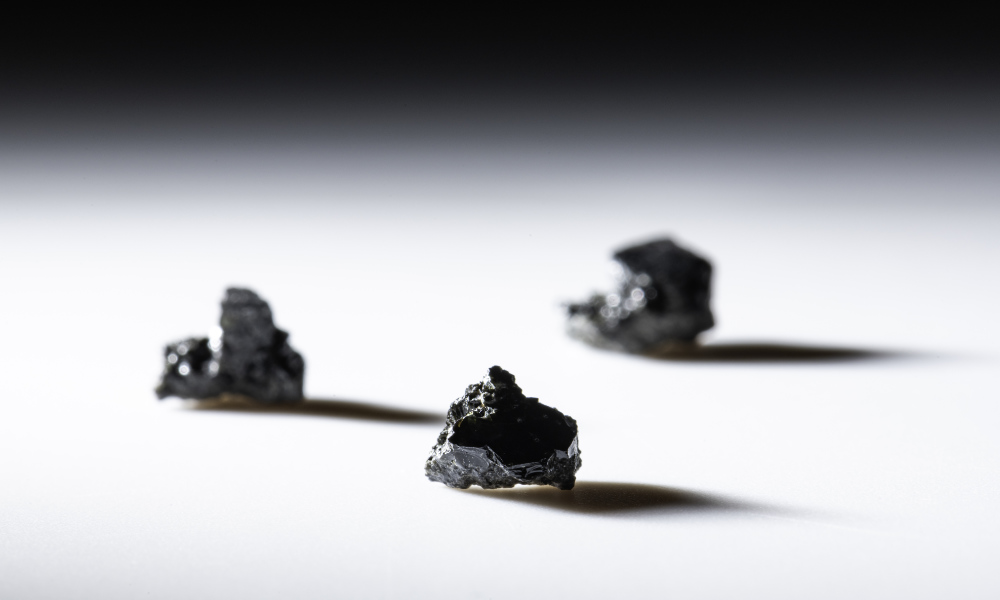 Three samples of lunar glass cast shadows on a white surface and dark background.