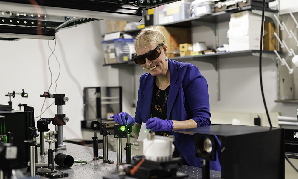 woman scientist waring safety glasses and gloves in a lab