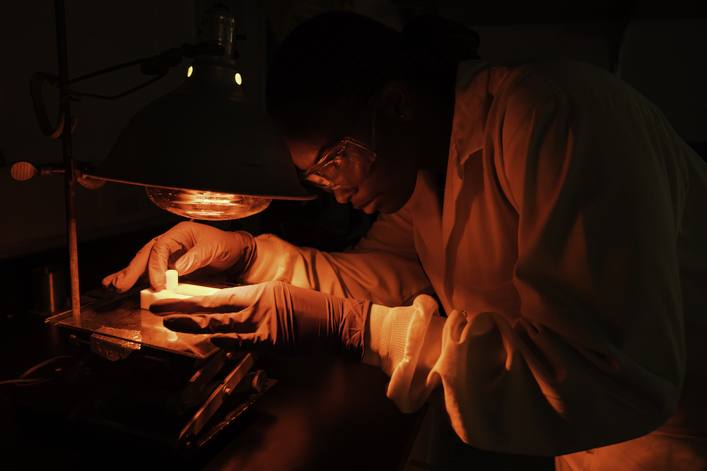 student lit by a red glow working in a lab