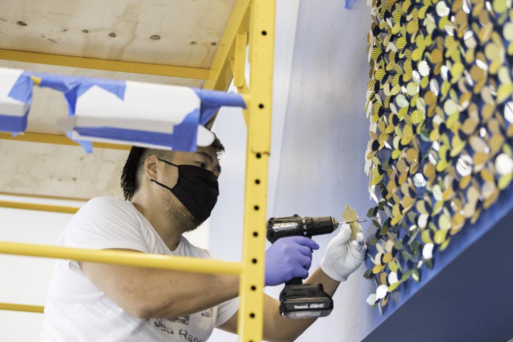 Jay Yan indossa una maschera mentre è su un'impalcatura che perfora i dischi nel muro.