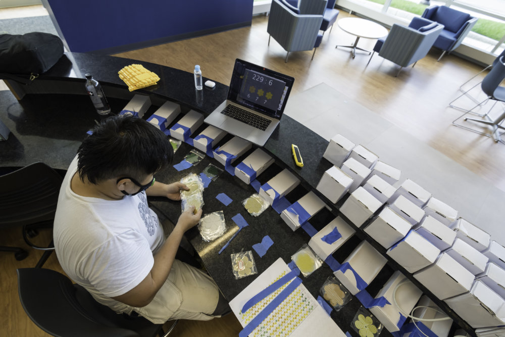 Inquadratura dall'alto dell'ordinamento di singoli pezzi di Jay Yan con un piano generale visualizzato su un laptop.