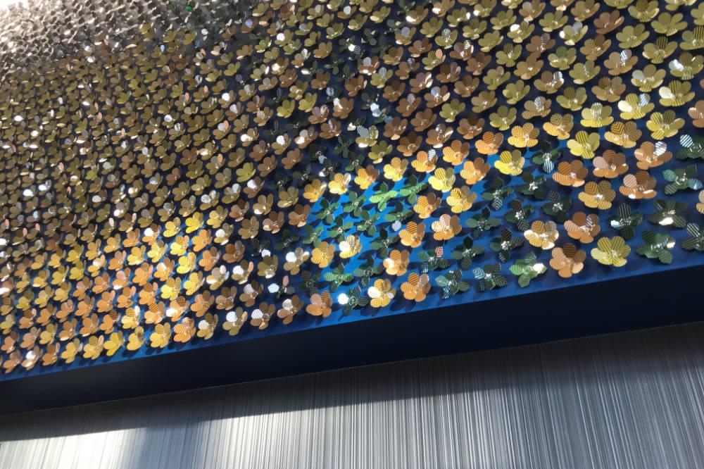 I dischi multicolori piegati in acciaio inossidabile riflettono i raggi del sole.