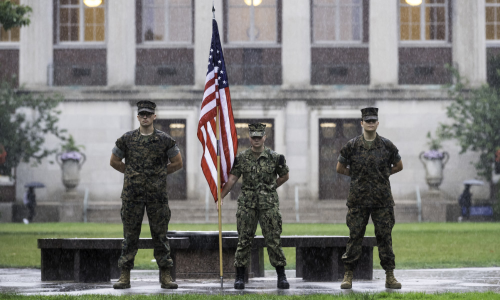 Three midshipmen in uniform stand on the Eastman Quad in the rain. The one in the center holds an American flag.